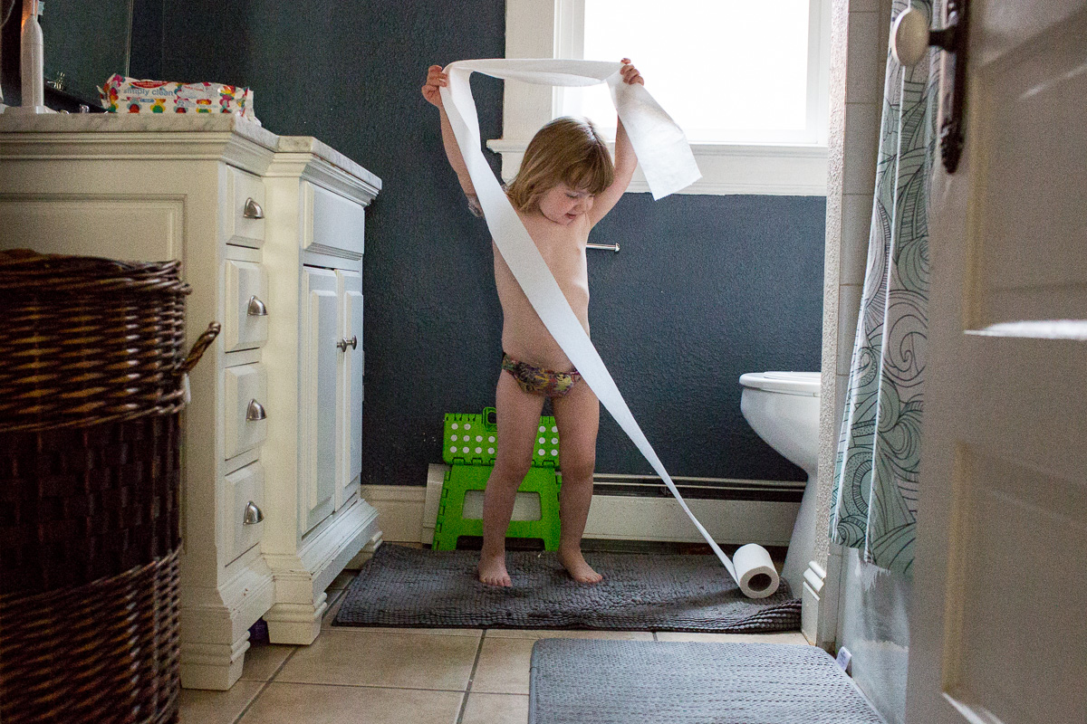 naked toddler playing with a roll of TP in a bathroom
