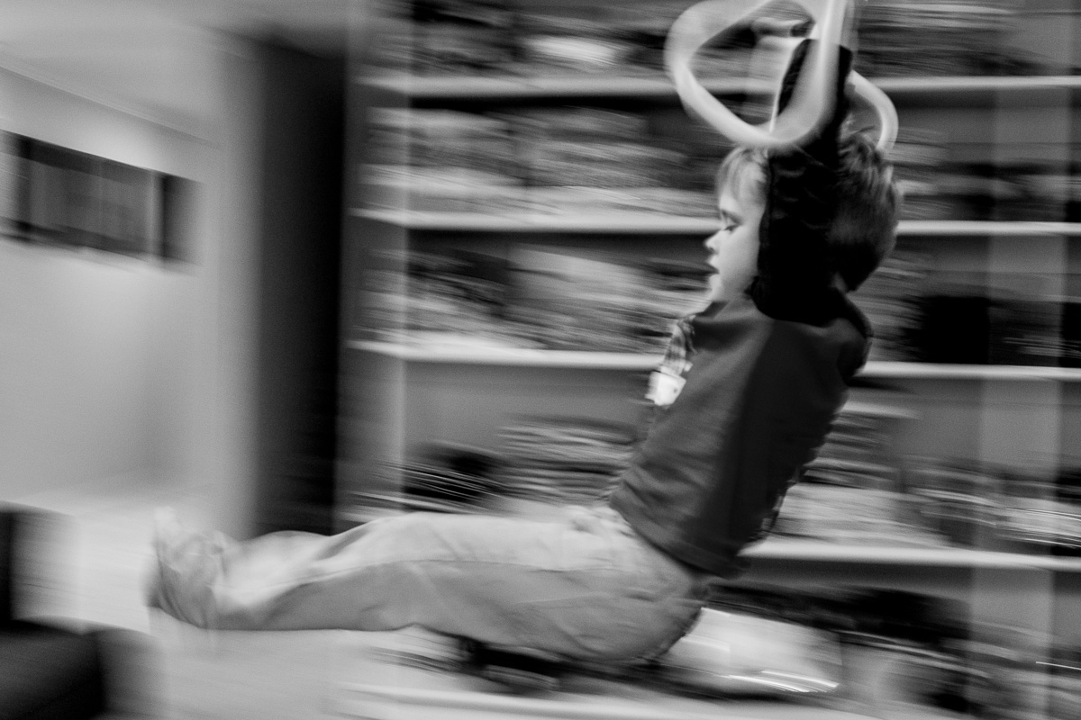 a boy swinging on rings with a blurred background showing motion