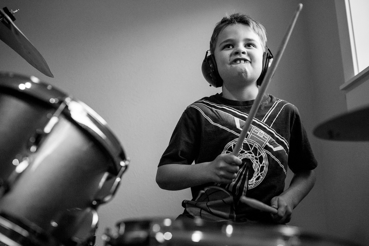 Young boy playing the drums and gritting his teeth while he plays