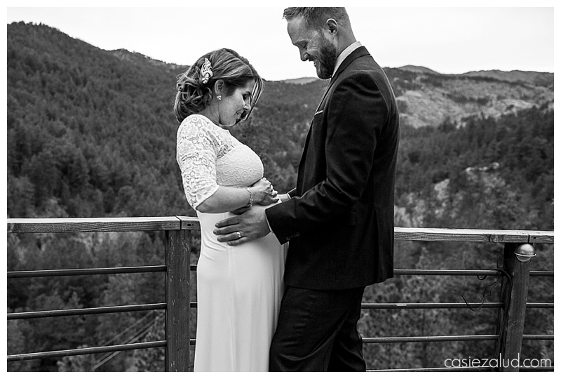 Pregnant bride and groom hold her belly as they look down at it in a portrait