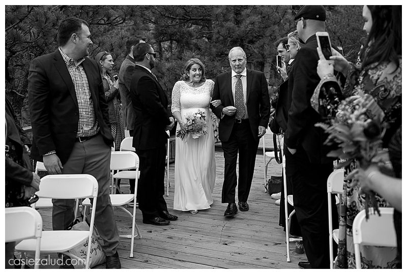Bride excitedly walking down the outdoor aisle with her father