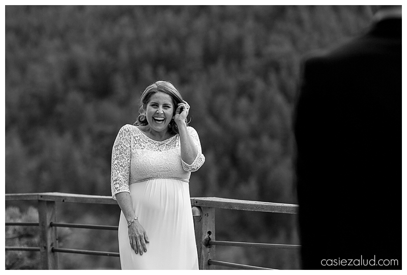 bride giggling and tucking her hair behind her ear as she turns to and see her groom for the first time
