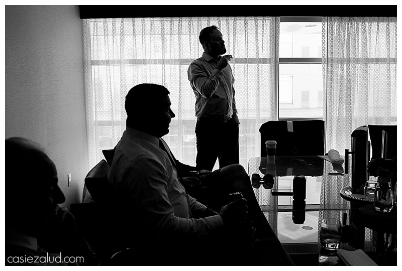 silhouette of groom's men getting ready and groom brushing his bread from underneath