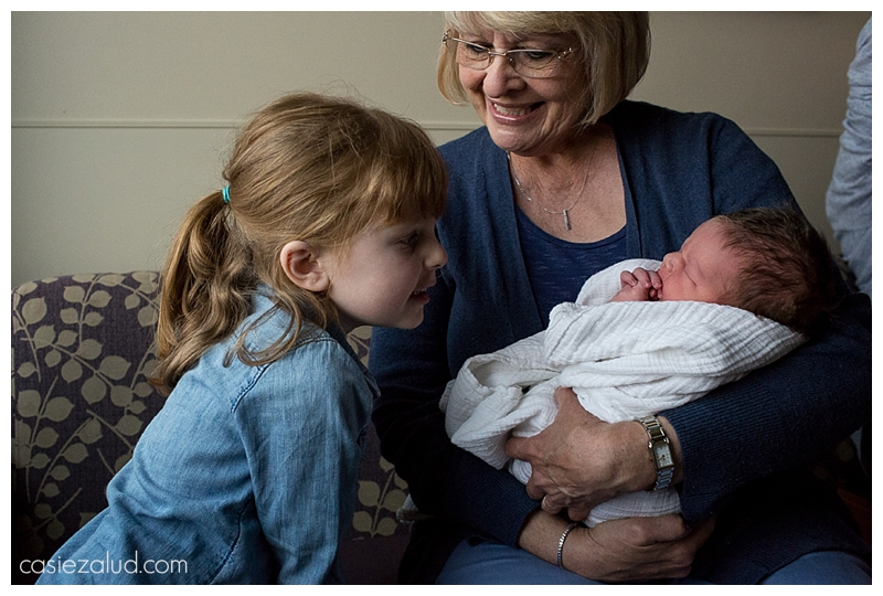 Grandma holds a swaddled newborn as a 4-year old sister checks him out for the first time