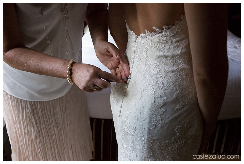 Mother using a knitting needle to put on all the button loops of her daughter's wedding dress