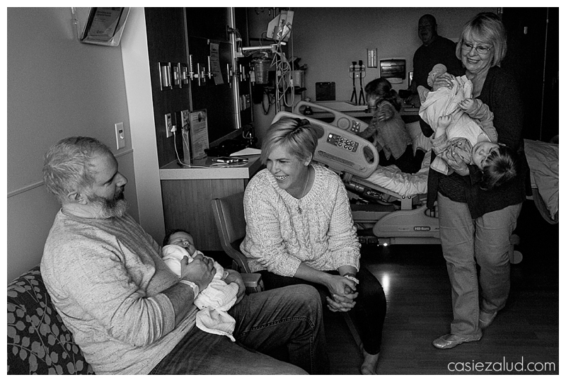 The chaos of a new family of five in a hospital room at St. Joe's in Denver. Kids climbing on beds and a still newborn being held.