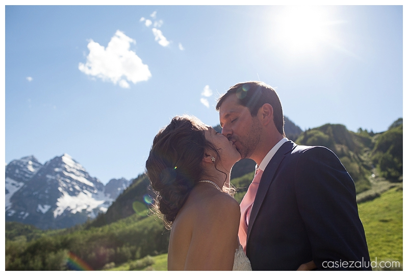bride and groom kissing with the Maroon Bells behind them and shooting into the sky with sunflare behind them