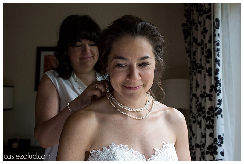mother putting pearls on her daughter's neck as she gets ready for her wedding