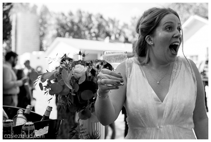 A surprised bride gasps as he is holding a glass of champagne at her farm wedding