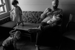 father holding newborn in hospital room while yawning and two other children climb on the furniture