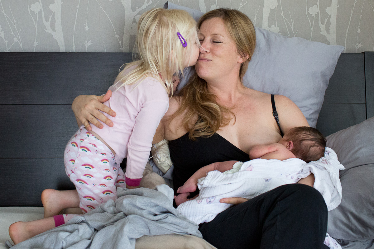 A mom in her bed breastfeeding her newborn as her toddler daughter jumps into bed and gives her a kiss