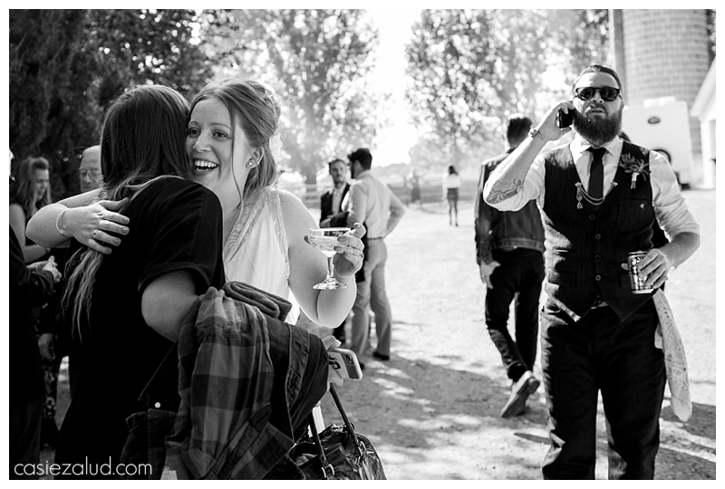 A bride hugging a guest with excitement as the groom walks up behind her on the phone