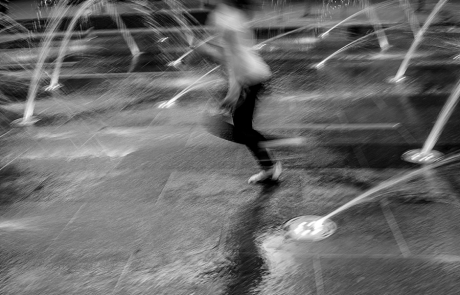 a girl running through a splash pad and you can see the motion of it