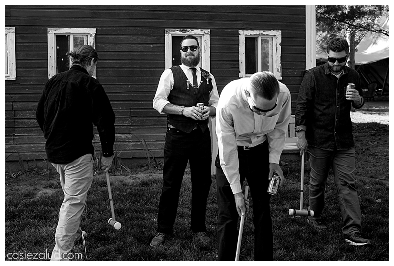Groomsmen playing croquet, with groom looking up at the camera with excitement when he sees his bride