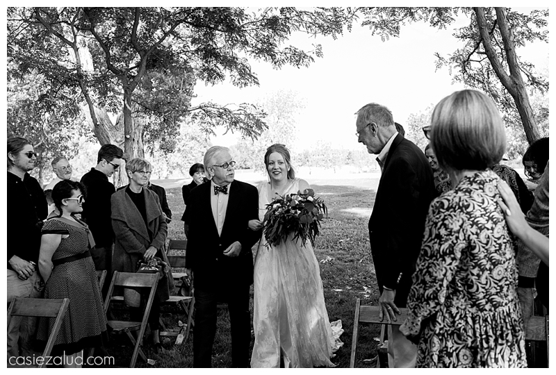 bride and her father walking down the aisle at an outdoor wedding