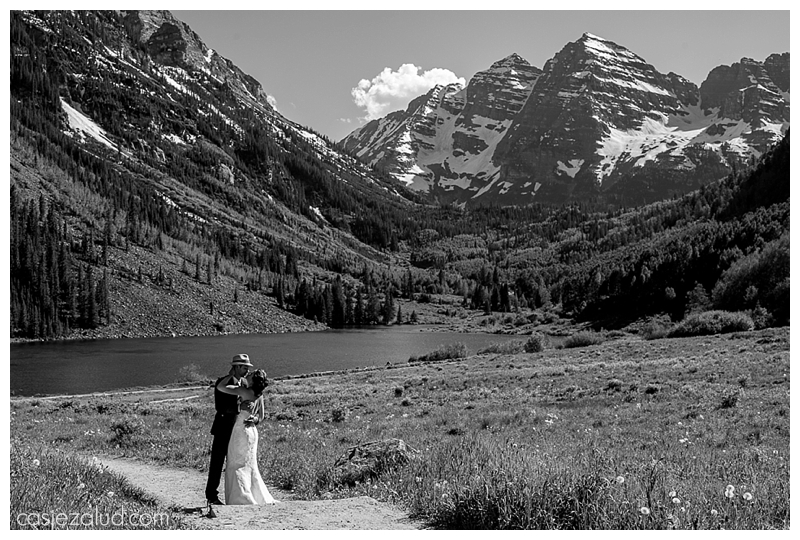 BW wedding couple portrait on trail in front of the Maroon Bells as they kiss