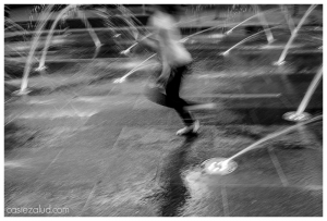 blurred photo of a girl running through a splash pad