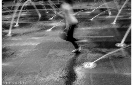 blurred photo of a girl running through a splash pad