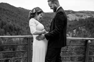Pregnant bride facing her groom as they both look down and hold her belly