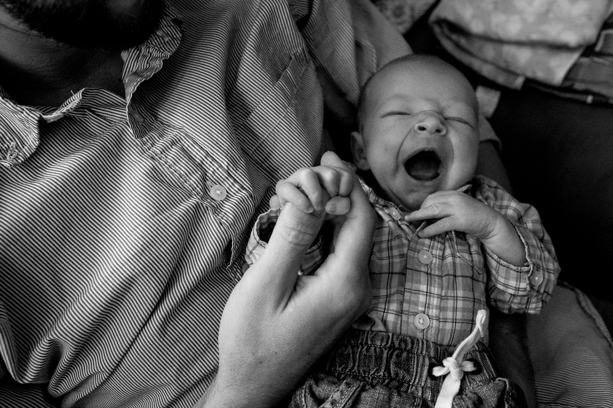 Dad holding newborn in his arms as his newborn holds his hand and yawns