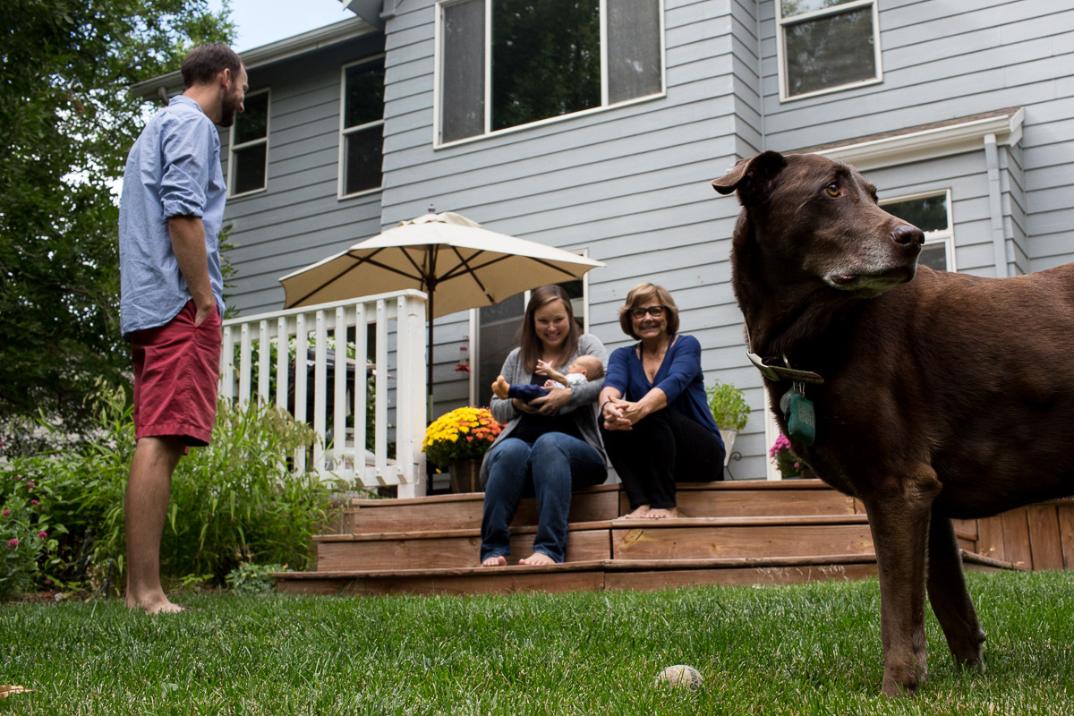 Dad, mom and grandma sit on the back deck with their newborn as the dog begs to play fetch