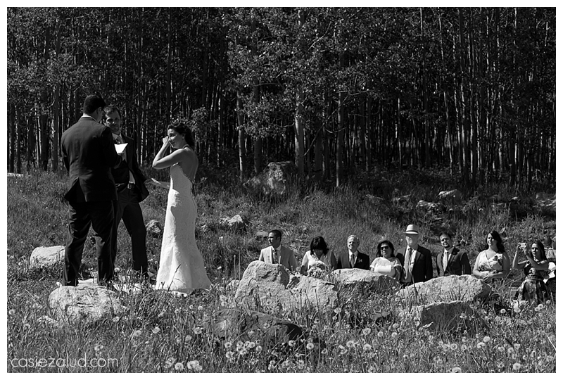a bride wiping a tear from her face as she weds her best best friend before her family at the Maroon Bells Amphitheater
