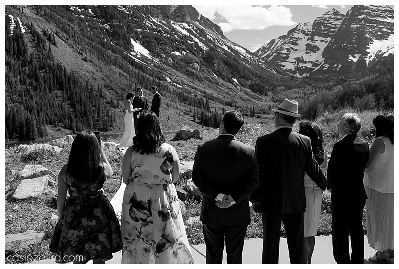 shot from the back seats of the amphitheater at the Maroon Bells overlooking the guests and looking at the bride and groom and Maroon Bells