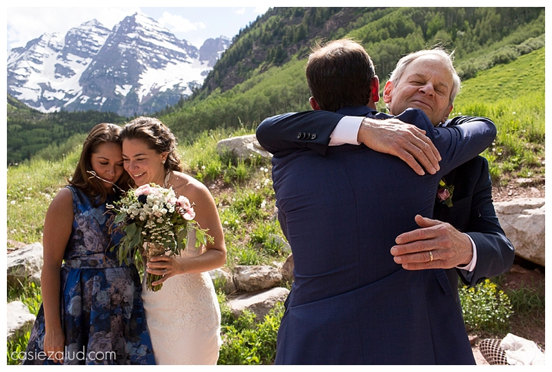 groom hugging dad while bride hugs sister in law at their maroon Bells wedding