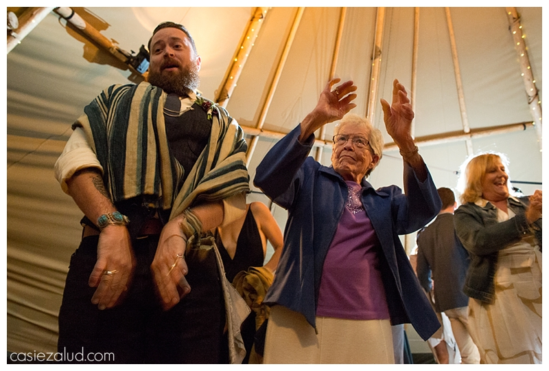 Groom and grandma dancing under a tepee at a Colorado farm wedding