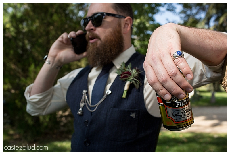 Groom talking on the phone showing off his cool style and pinky ring