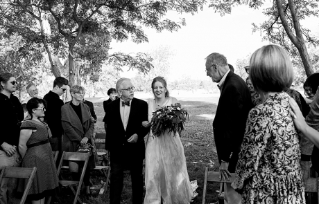 A Father walking the bride down the asile as the mom watches and tears up and the bride looks at the mom