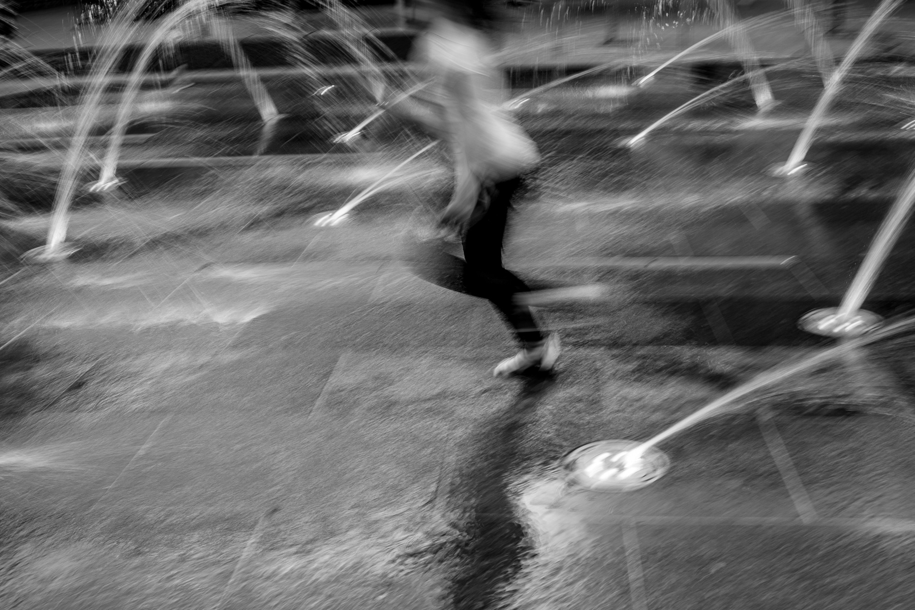 girl running through fountain with motion blur