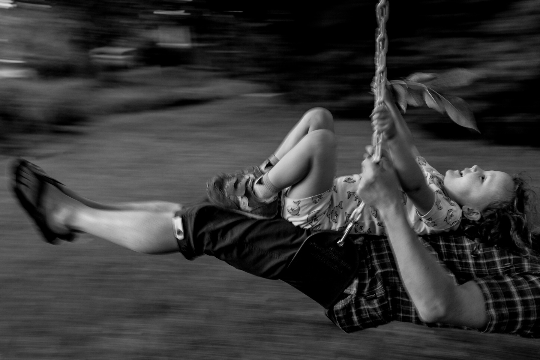 girl holding a branch of leaves sitting on man's lap on a swing can see the motion of moving