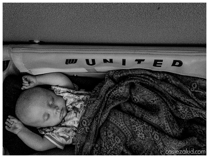Infant sleeping in a United airlines bassinet
