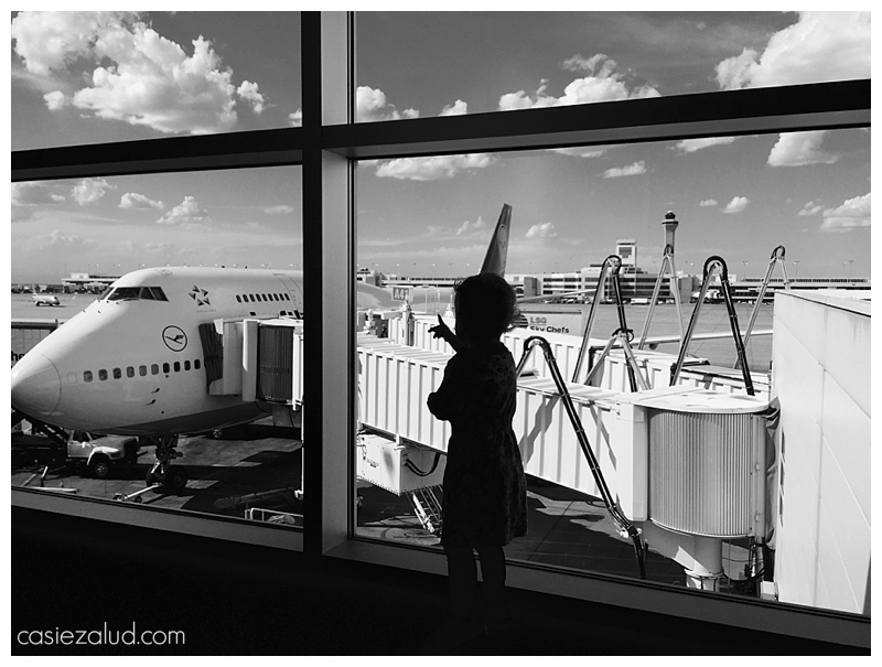 silhouette of a toddler looking out the window at a plane at the airport