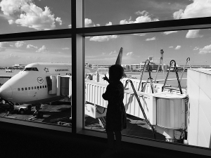 silhouette of toddler looking at a plane at the airport