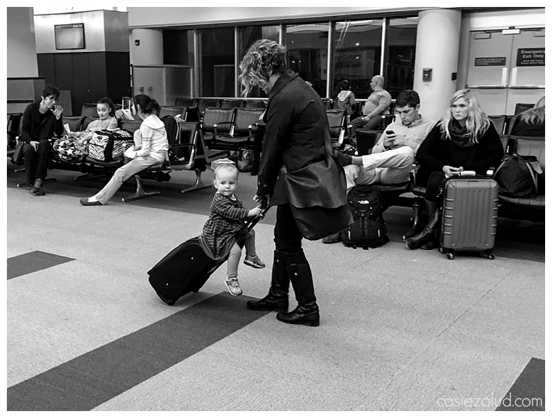 mom pulling a toddler on a suitcase in an airport