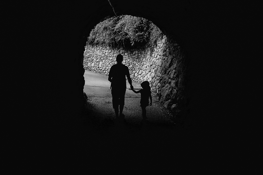 silhouette of adult and child holding hands leaving a tunnel