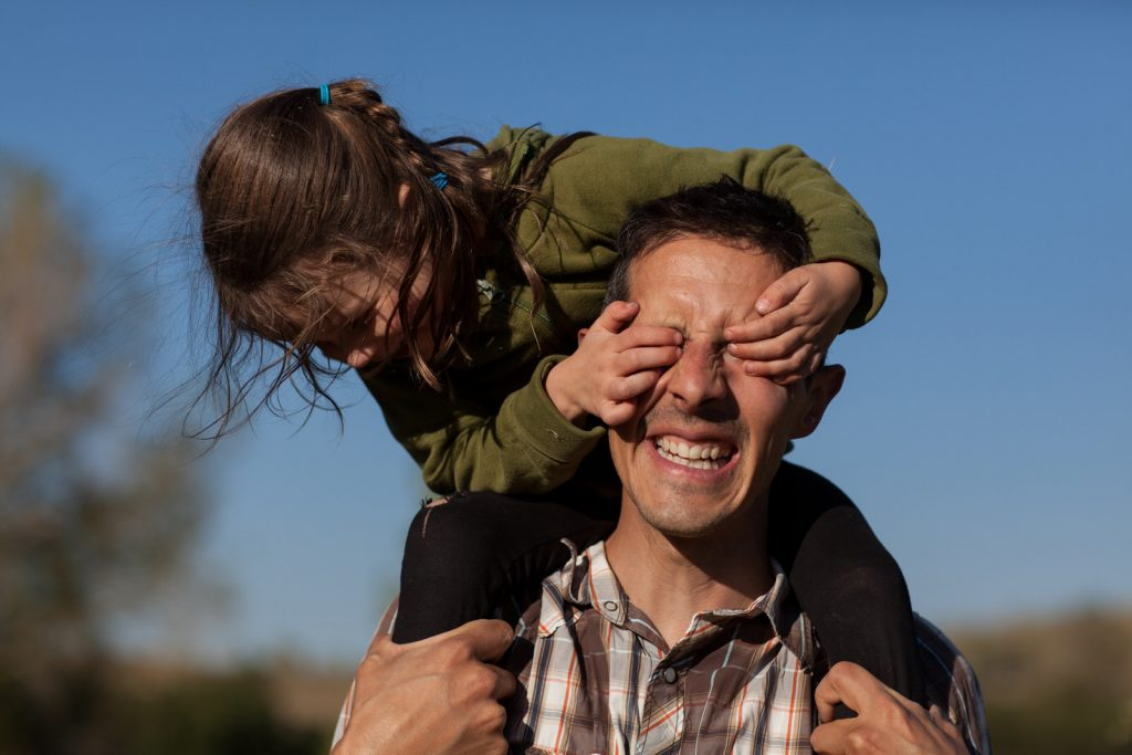 Little girl on dad's shoulders holding on by squeezing his eyeballs