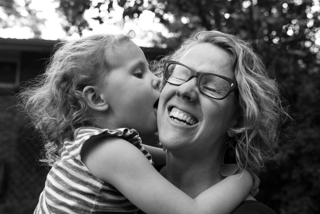 CASIE Zalud Boulder Colorado family photographer being kissed and squeeze hugged by her daughter