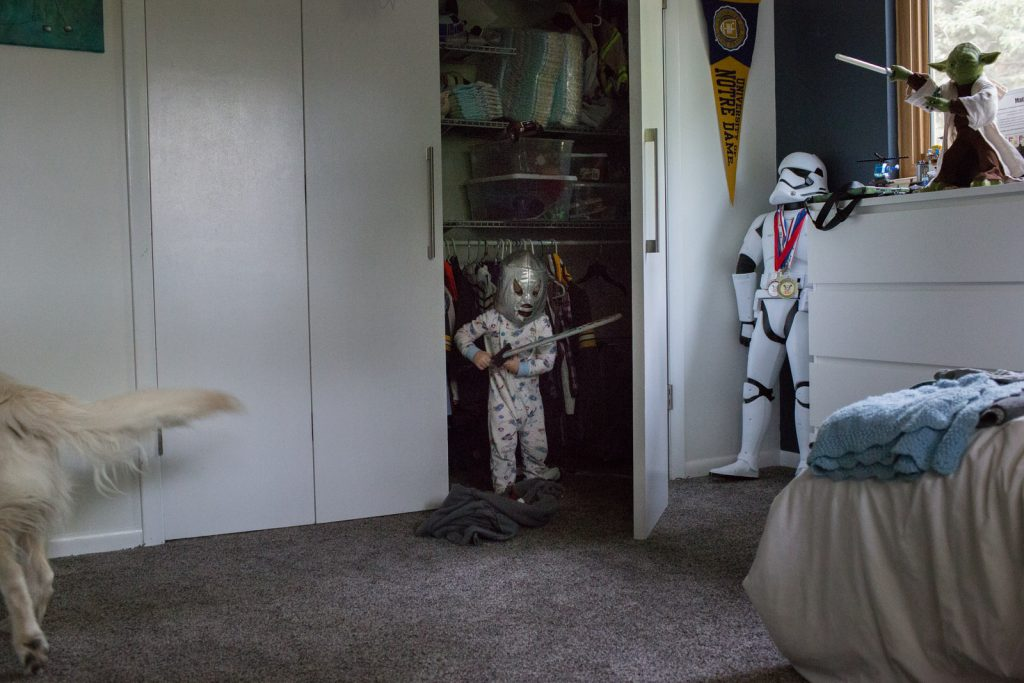 During a Boulder Family Photo session a little boy wearing storm trooper costume coming out of closet with light saber.