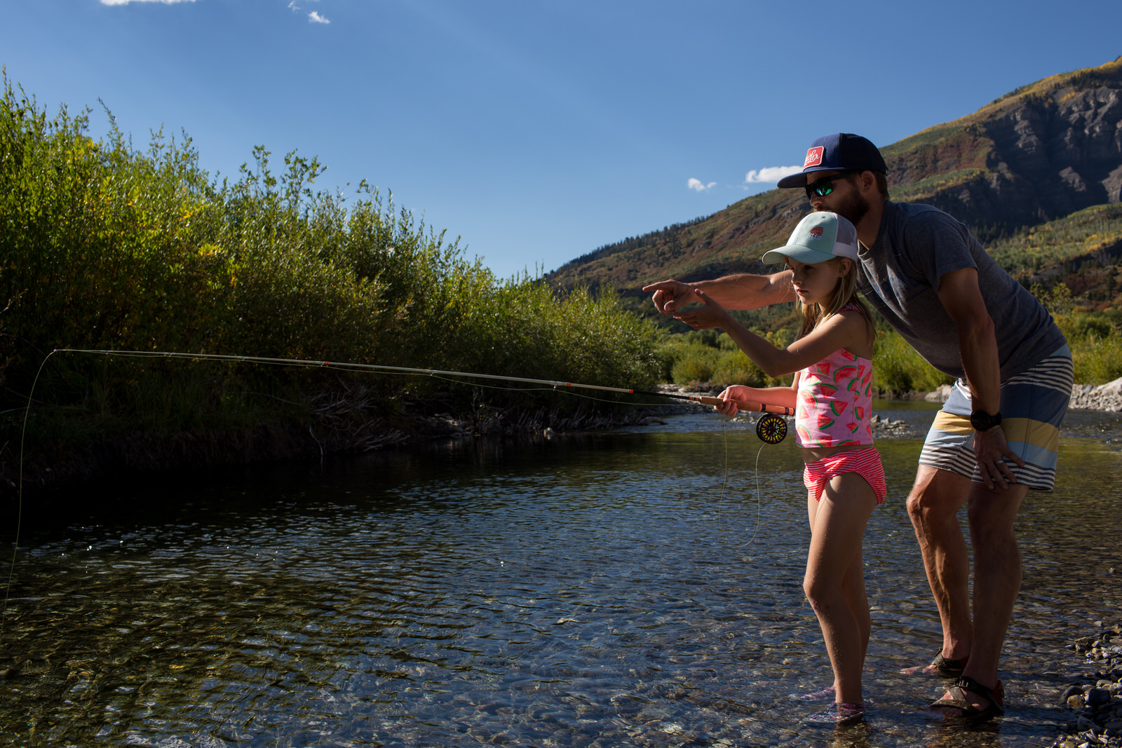 dad helping daughter fly fish in aspen on a river on a sunny day