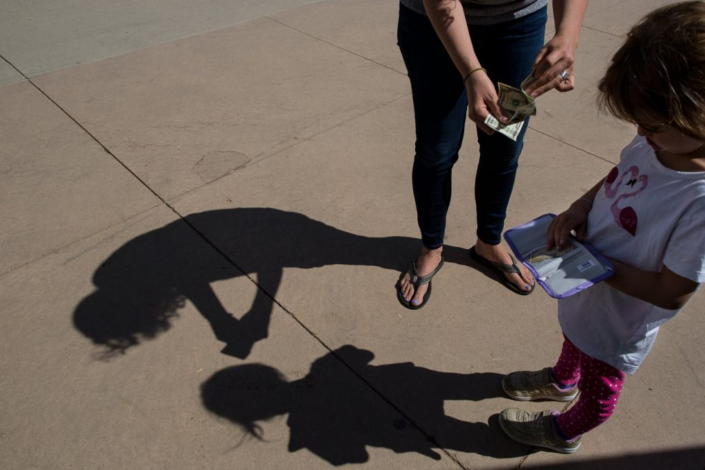 shadow on ground of mom giving child money to put in little wallet during a family photo session