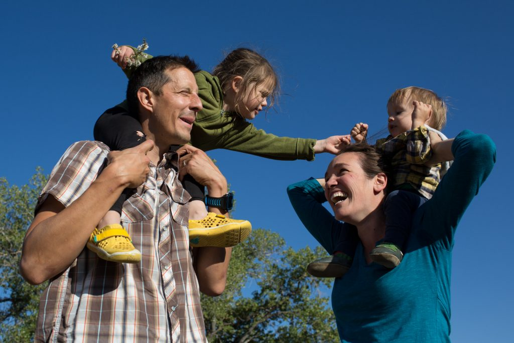 family of four with kids on shoulders of parents and having a tickle fight during a boulder family photographer session