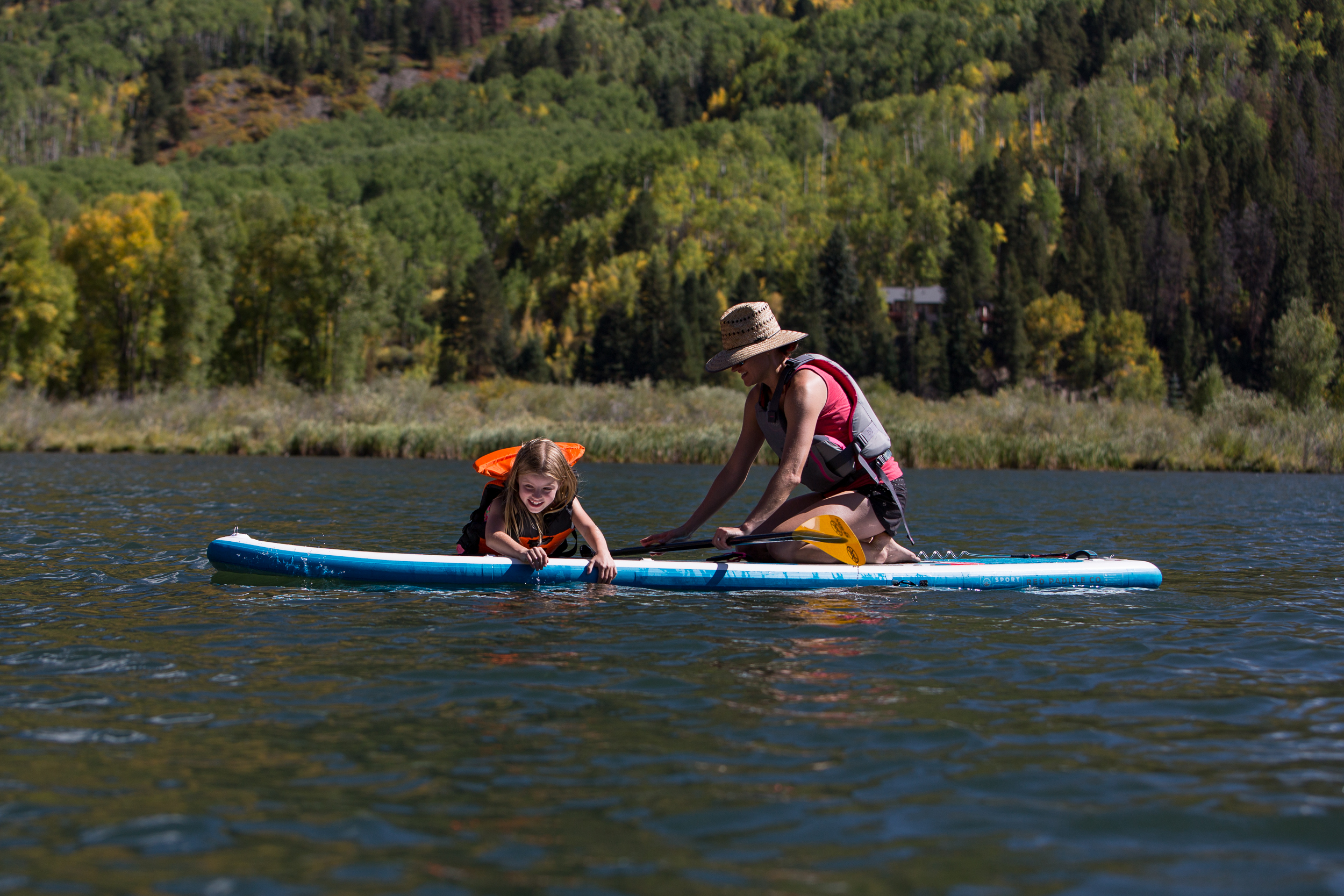 mom and daughter on paddleboard at marble colorado during a vacation photo session