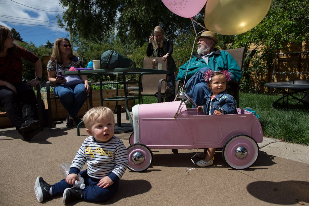 little girl in pink metal car with pink balloon.