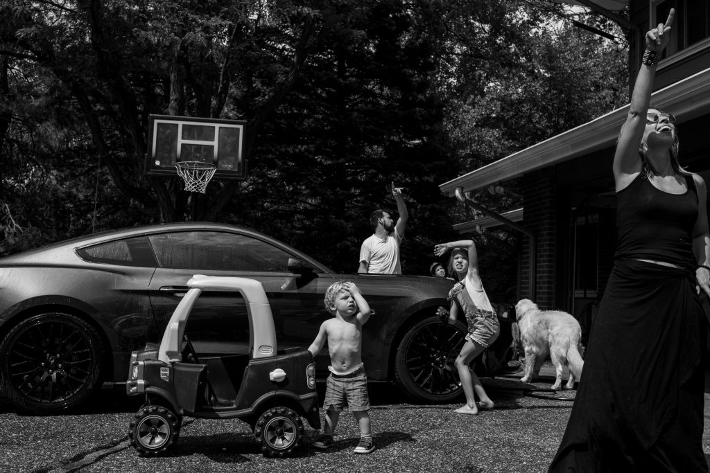 entire family looking up at something in the sky in their driveway during a family photo session in boulder