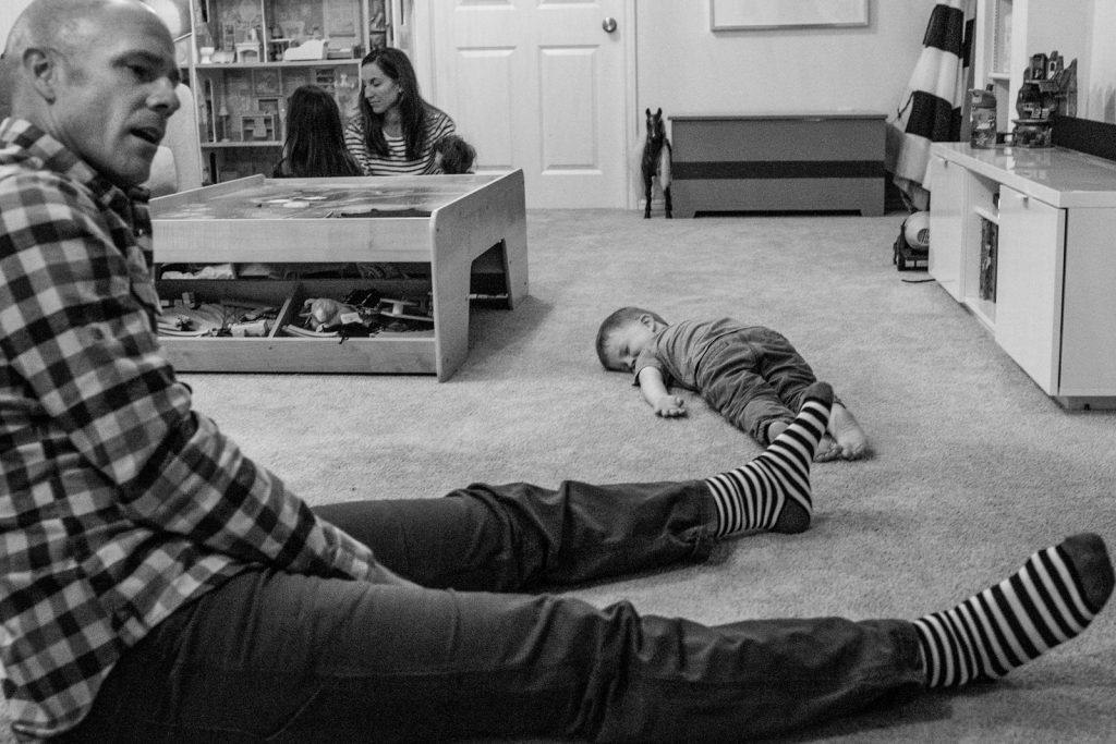 exhausted kid laying face down on living room floor during a boulder family photography session