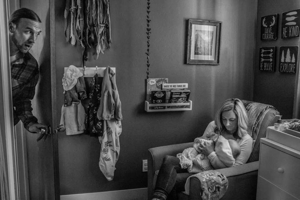 dad peeking in through the door to nursery where mom is breastfeeding baby during newborn photography session with Casie Zalud