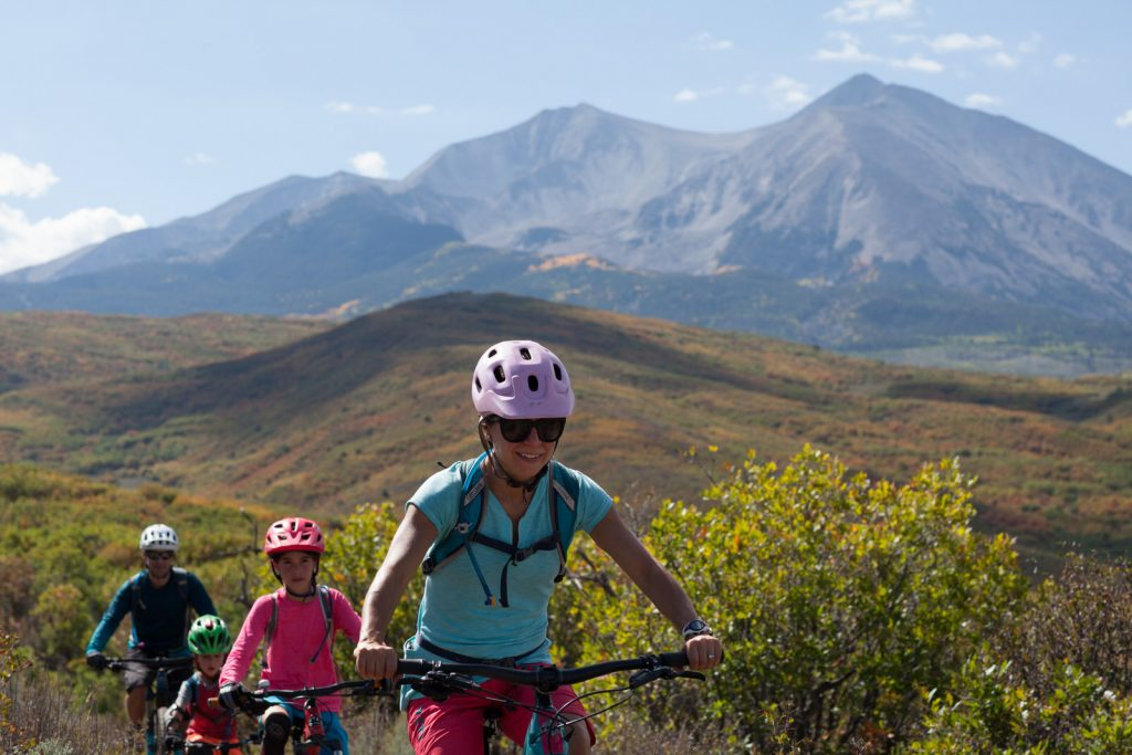 mom leads her family of four on mountain bikes in the fall with Mt Sopris